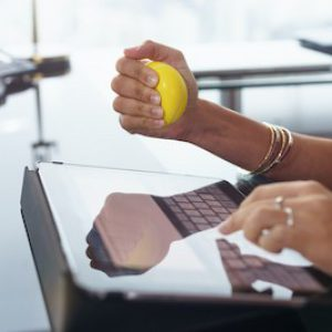 stressed-office-worker-with-anti-stress-ball-P9E76NX.jpg